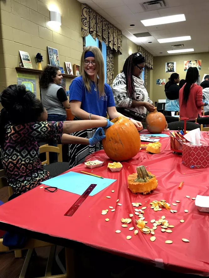 A tutor helps students with a pumpkin-based math activity
